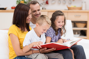 familie liest gemeinsam in einem buch