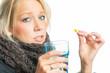 Blonde Frau mit Kapsel und Wasserglas