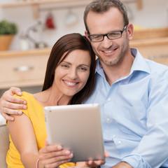 glückliches paar schaut auf tablet