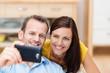 lachendes paar schaut auf smartphone