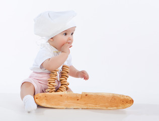 Little baker baby girl with a long loaf and bagels.