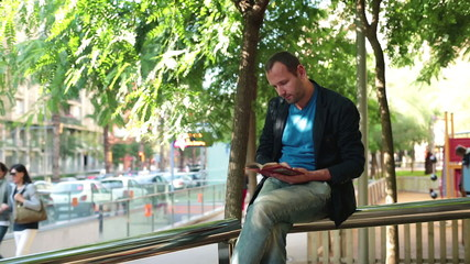 Young man reading a book sitting on handrail in city