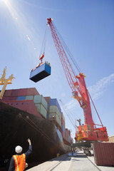 Worker guiding crane unloading container ship at commercial dock