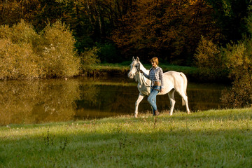 Young woman with horse in the lake