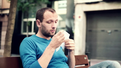 Sick man blowing his nose in the tissue in city