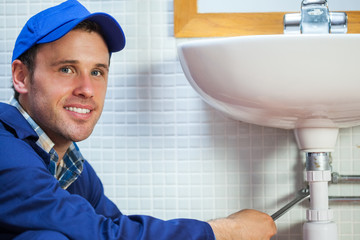 Attractive cheerful plumber repairing sink