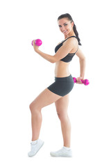 Side view of smiling active woman training with dumbbells