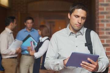 Concentrated male mature student holding his tablet standing in