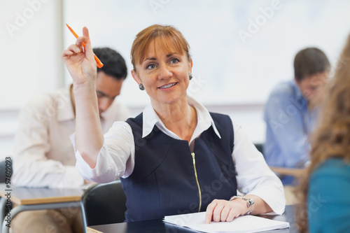 Female mature student raising her hand