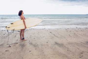 Calm woman carrying surfboard on the beach
