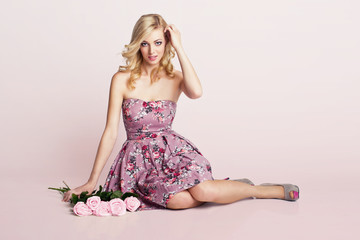 beautiful blonde girl sitting next to the flowers