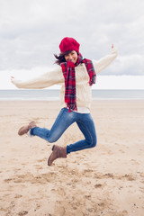 Woman in stylish warm clothing jumping at beach