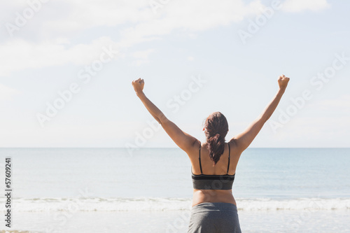 Content brunette woman standing on the beach