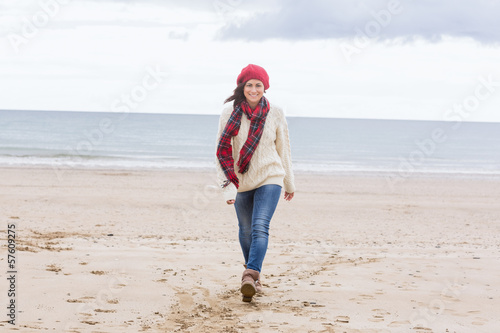 Pretty woman in stylish warm wear at beach
