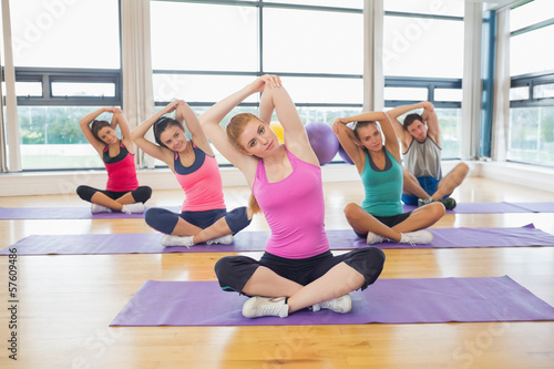 Portrait of fitness class and instructor stretching hands on yog
