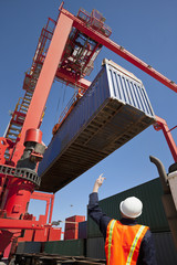 Worker guiding crane lifting cargo container at commercial dock