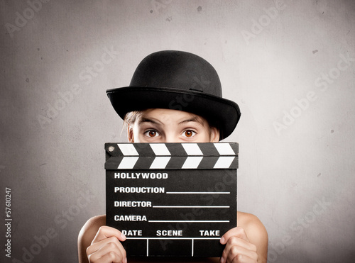 little girl holding a movie clapper board
