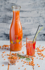 Sea buckthorn berries juice on the glass wiyh flower