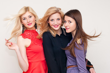 Three happy beautiful fashion women studio shot