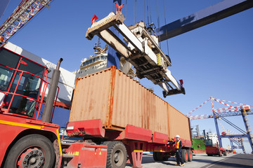 Crane unloading cargo container onto lorry at commercial dock