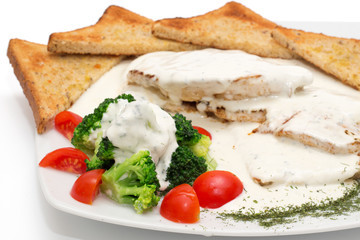 Chicken with gorgonzola, vegetables and bread on the plate