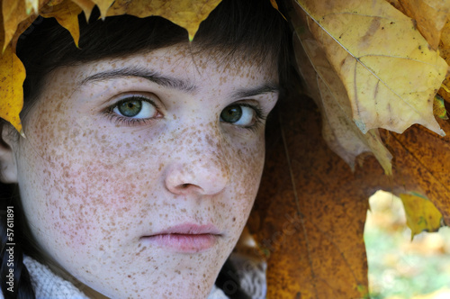 close-up portrait of freckled teenage girl in autumn park