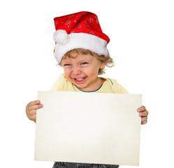 Kleiner Junge mit Weihnachtsmütze hält eine weiße Tafel