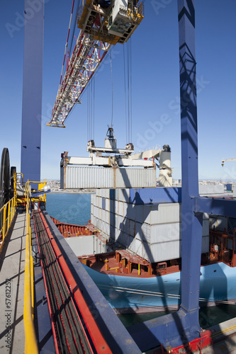 Crane loading cargo containers onto container ship at commercial dock
