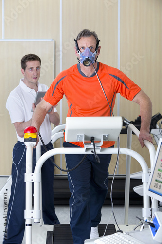 Sports scientist with digital tablet monitoring runner with mask on treadmill in laboratory