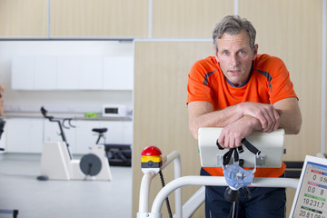 Portrait of runner holding mask and leaning on treadmill in sports science laboratory