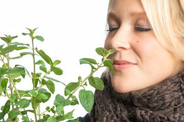 Blonde Frau riecht an Pfefferminzpflanze