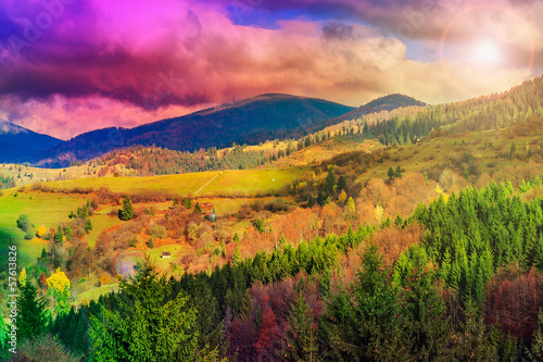 light  beam falls on hillside with autumn forest in mountain - 57613826