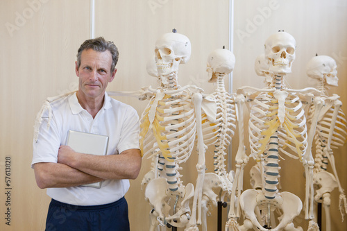 Portrait of confident sports scientist standing next to skeleton models