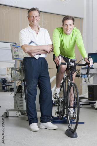 Portrait of confident sports scientist and cyclist on exercise bike in laboratory