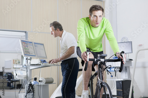 Sports scientist at computer and cyclist on exercise bike in laboratory