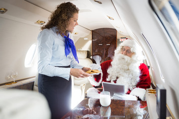Smiling Airhostess Serving Cookies To Santa In Private Jet