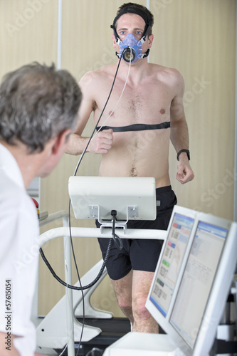 Sports scientist at computer watching runner with mask on treadmill in laboratory