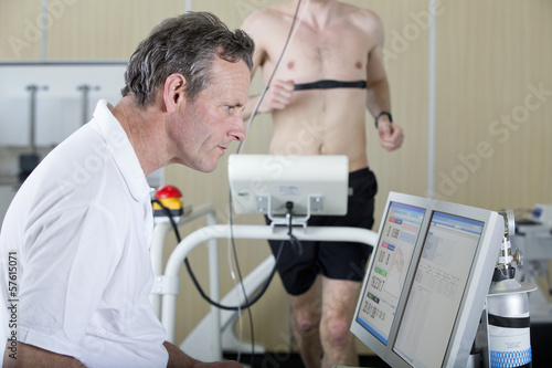 Sports scientist at computer and runner on treadmill in laboratory