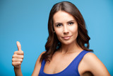 Smiling woman showing thumb up gesture, over blue