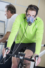 Cyclist with mask on exercise bike in sports science laboratory