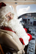 Man In Santa Costume Sitting In Private Jet's Cockpit