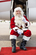 Santa Holding Milk Glass While Sitting On Private Jet's Ladder