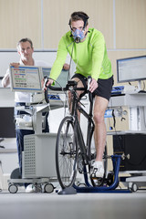 Sports scientist monitoring cyclist with mask on exercise bike