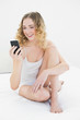 Pretty happy blonde sitting on bed holding smartphone