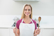 Casual smiling blonde showing wooden spoon and whisk