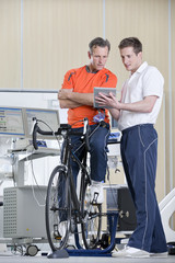 Sports scientist and cyclist on exercise bike looking down at digital tablet