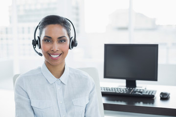 Attractive female agent wearing headset smiling at camera