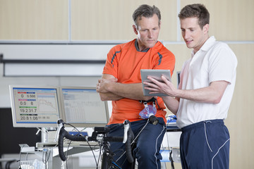 Sports scientist and cyclist on exercise bike looking down at digital tablet in laboratory