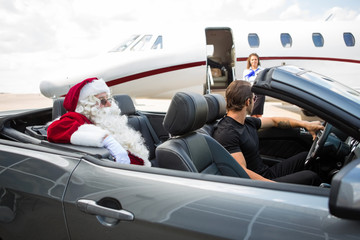 Santa And Chauffeur In Convertible While Airhostess Against Priv