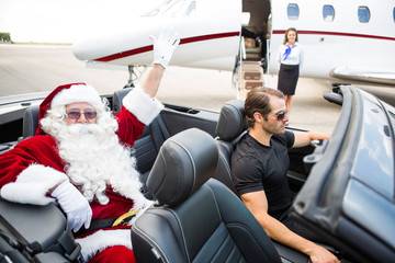 Santa Waving Hand While Chauffeur Driving Convertible Against Pr